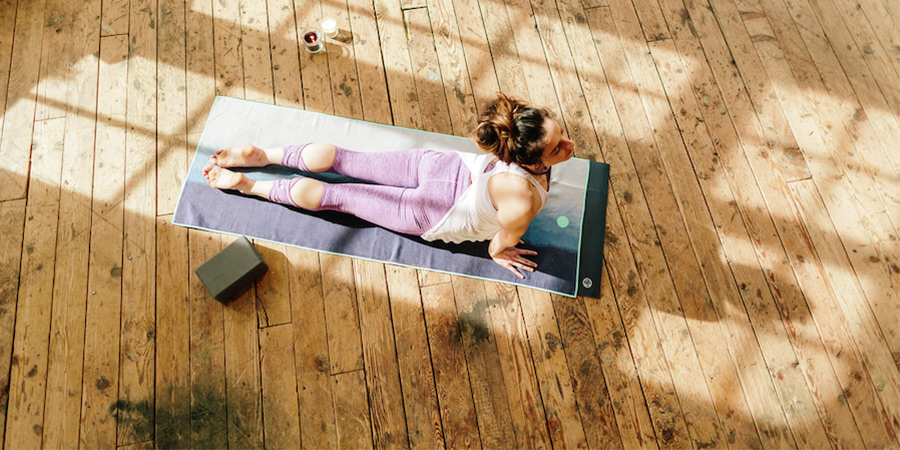 Woman lying on a yoga mat in a pose