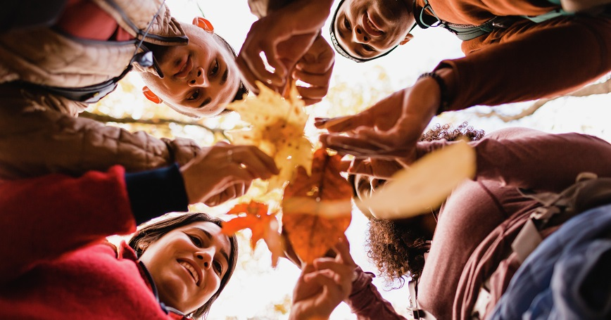 Group of people standing in a circle holding autumn leaves