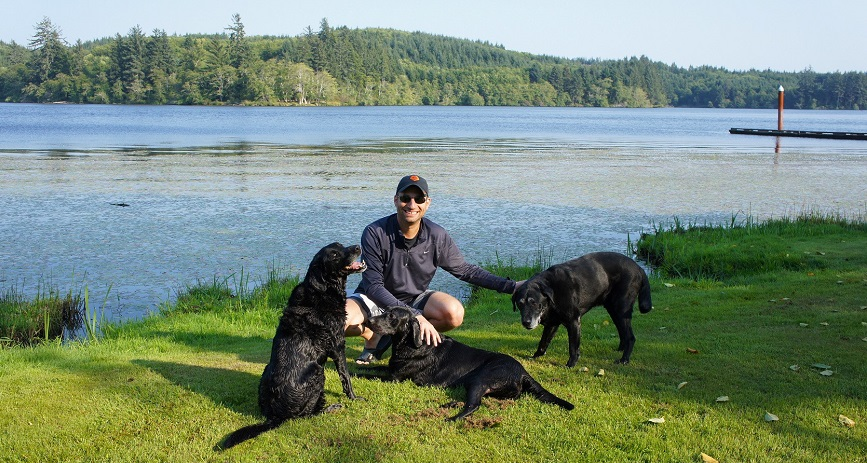 Image of Dan Shull with his three black lab dogs